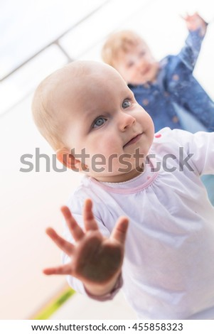 Baby girl looking through a window - stock photo
