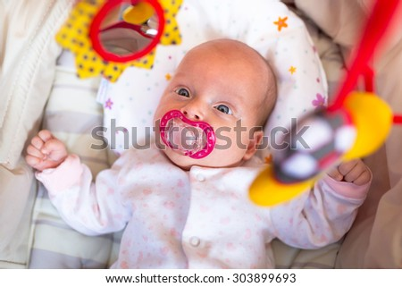 Baby girl lying down in the cradle - stock photo