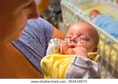 Baby girl lying down in the cradle with toys - stock photo