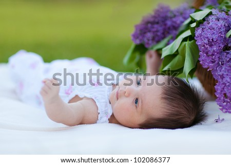 Baby girl lying in park with lilac bouquet in basket - stock photo