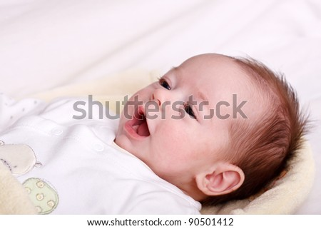 Baby girl lying on a soft blanket and watching - stock photo