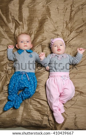 Baby girl lying on bed in bedroom with golden linens. Charming 5-month-old girl and boy smiling, grimacing and hold hands.  Home interior in background. - stock photo