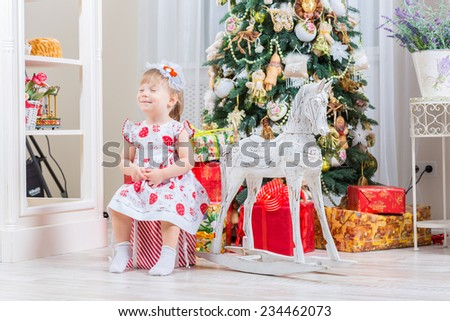 baby girl next to a horse rocking near a Christmas tree - stock photo