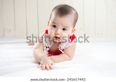 Baby girl on her stomach. Looking up with surprised expression. asian baby in the room - stock photo