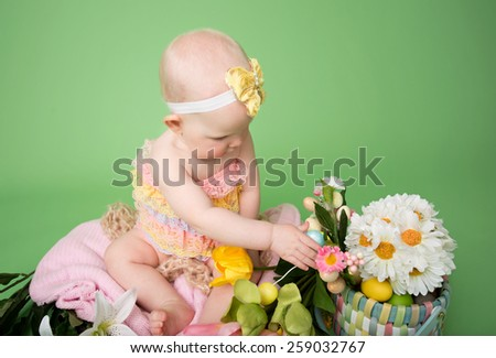 Baby girl on pink background holding an easter egg - stock photo