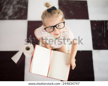 Baby girl on potty with notebook - stock photo