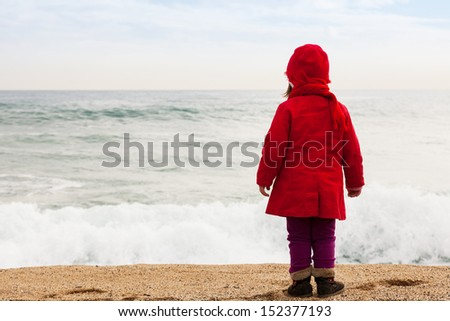 Baby girl on sand beach in cold windy day - stock photo
