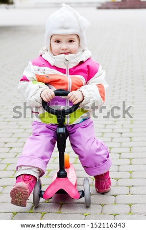 baby girl on scooter in the park - stock photo