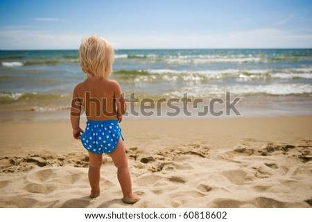 Baby girl on the beach looking at the sea. - stock photo