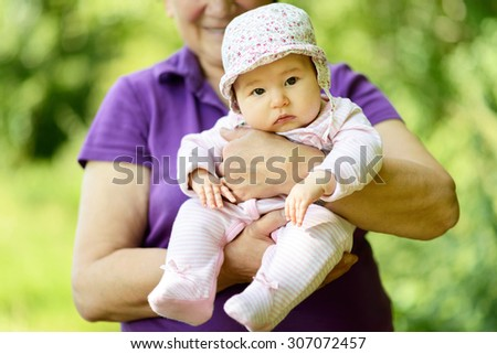 Baby girl on the hands of her grandmother in nature - stock photo