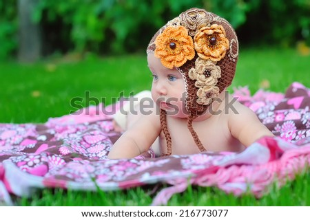 baby girl outdoors in a brown knitted cap - stock photo
