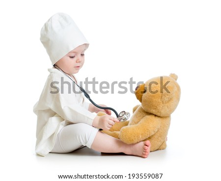 baby girl playing doctor with plush toy - stock photo
