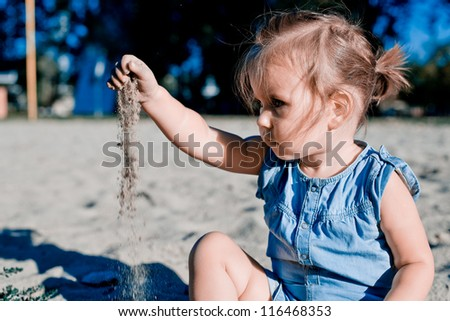 Baby girl playing in sand - stock photo