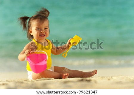 Baby girl playing in the sand on the beach. Ocean as background - stock photo