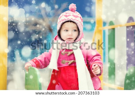Baby girl playing on winter playground - stock photo