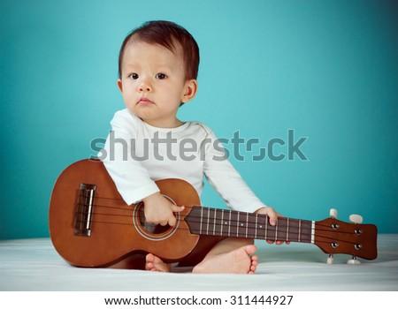 Baby girl playing ukulele (soft focus on the eyes) - stock photo