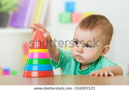 Baby girl playing with a pyramid toy - stock photo