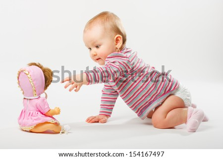 Baby girl playing with doll - stock photo