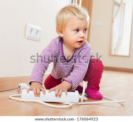 Baby girl playing with electrical extension  on floor at home - stock photo