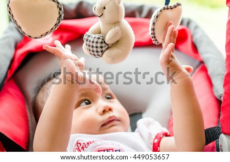 Baby girl playing with mobile in the cradle - stock photo