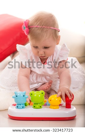 Baby girl playing with musical toy animals home - stock photo