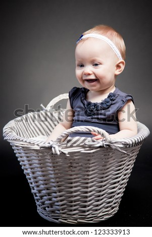 Baby girl posing in a vintage basket. The look at her face expresses her exploration of the world. - stock photo
