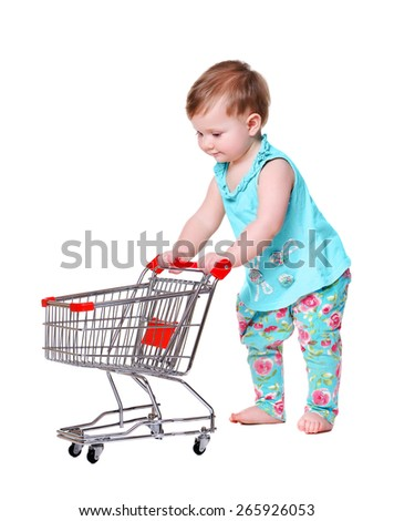 baby girl pushing shopping trolley - stock photo