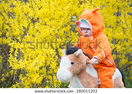 Baby girl ridding horse - stock photo