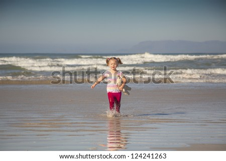 baby girl running through the sea on the beach with a teddy under her arms. - stock photo