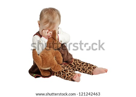 Baby girl sits and plays peekaboo with stuffed animal. She wears a brown velvet embroidered dress with leopard print pants. Isolated/cut out on white background, vertical, copy space. - stock photo