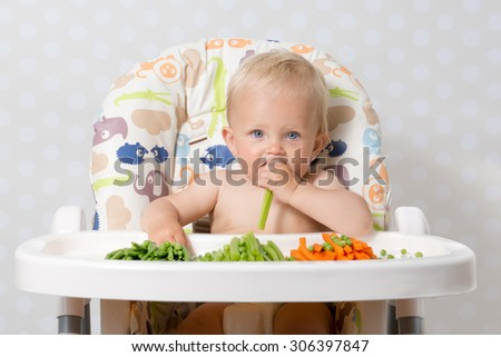 Baby girl sitting in a highchair eating raw, seasonal vegetables: carrots, beans, peas, celery - stock photo
