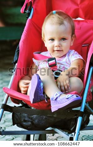 baby girl sitting in red stroller - stock photo
