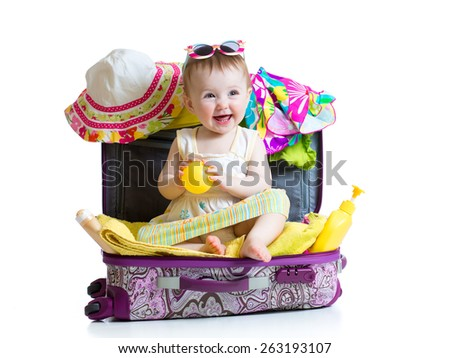 Baby girl sitting in suitcase with  things for vacation travel isolated - stock photo