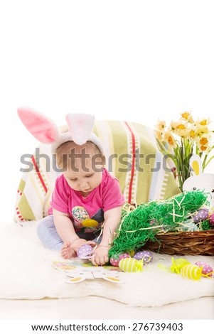 Baby girl sitting on blanket and playing with Easter eggs against white background - stock photo