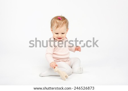 baby girl sitting with a wooden giraffe toy over white background in studio - stock photo