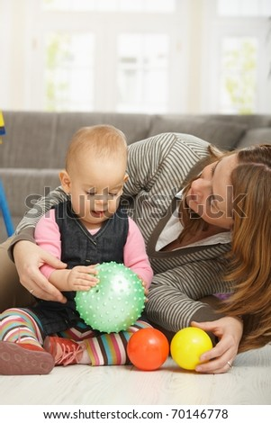 Baby girl smiling holding ball in hands, mum cuddling baby.? - stock photo