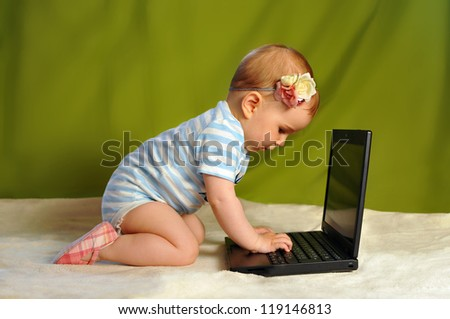 Baby girl surfing the web (using PC) - stock photo