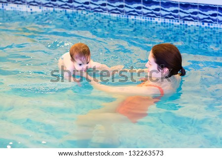 Baby girl swimming with her mother in a pool - stock photo
