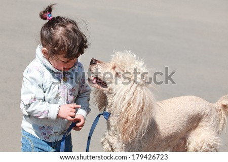 baby girl talking with a dog - stock photo
