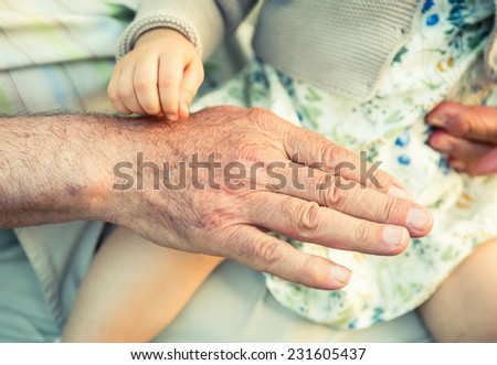 Baby girl touching hand of senior man. Two different generations concept. - stock photo