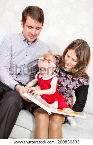 Baby girl turning pages of book while parents reading - stock photo