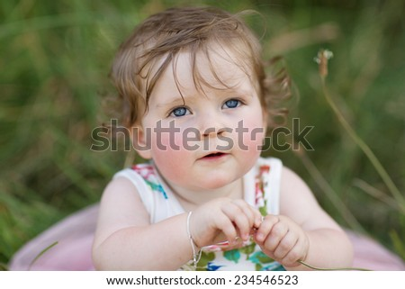Baby Girl twelve months old on grass in park - stock photo