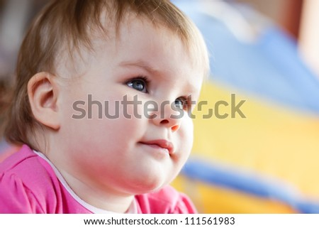 Baby girl watching tv at home - stock photo