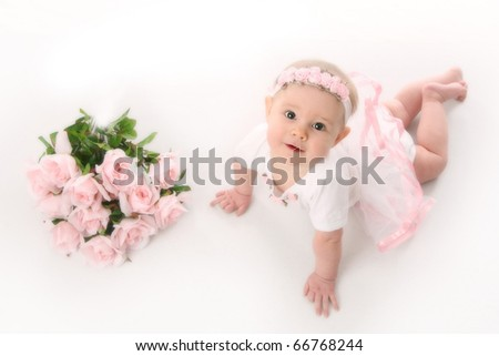 Baby girl wearing a ballet costume lying on her belly next to a bouquet of soft pink roses - stock photo