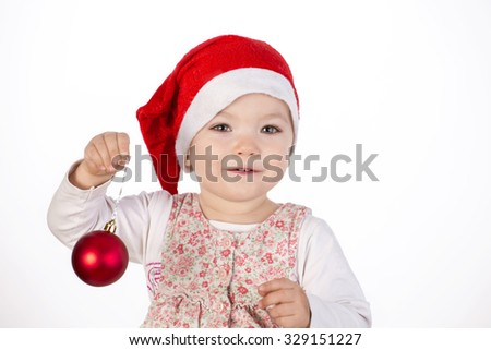 baby girl wearing santa hat on white isolated background with chrismas ball - stock photo