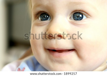 Baby girl with big clear blue eyes playing happily - stock photo