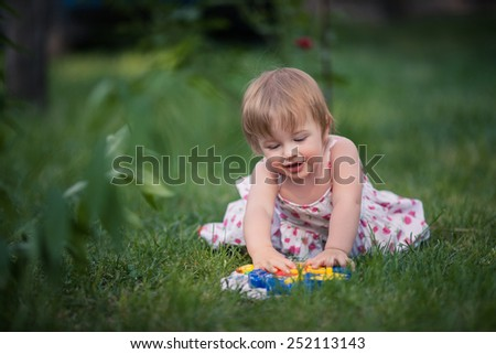 baby girl with blue eyes and blond hair sits on the grass and plays toy. She dressed on white with floral pattern summer dress. Background is diffused by green, brown and blue colors - stock photo