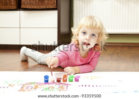 Baby girl with blue eyes paint in the floor - stock photo