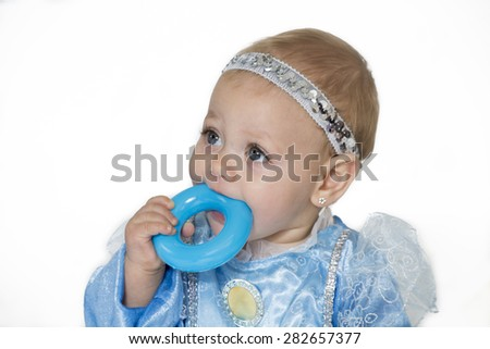 baby girl with blue ribbon, put blue ring toy in her mouth - stock photo