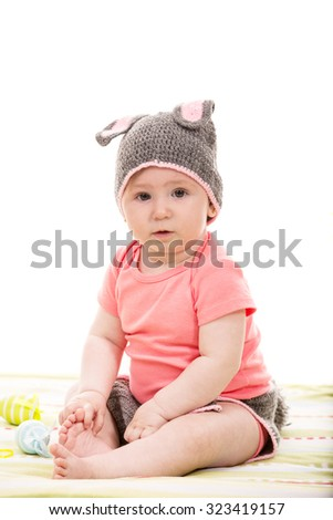 Baby girl with croched bunny hat  and Easter eggs - stock photo